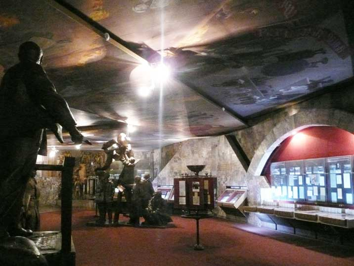 The exposition of the Lenin Museum combines sculptures and ceiling paintings depicting Soviet history plus other artifacts like documents and photos