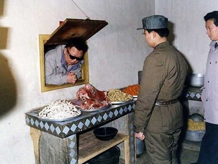 Kim Jong Il looking at food in the kitchen of a restaurant