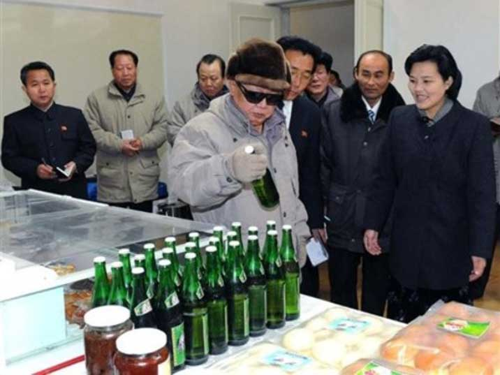 Kim Jong Il looking at a bottle of beer in a North Korean brewery