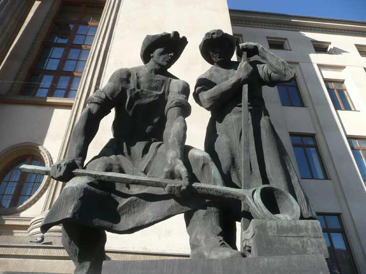 Sculpture of metal workers casting iron in front of the Krakow University of Science and Technology building