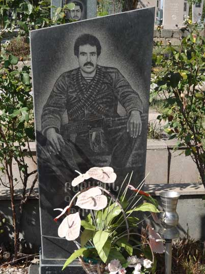 Stepanakert Memorial complex grave with a photograph of a Armenian soldier sitting down with a machine gun on his lap