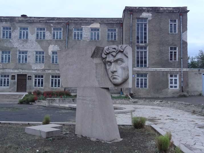 The main building of the Stepanakert State University in bad condition with a communist era monument in front