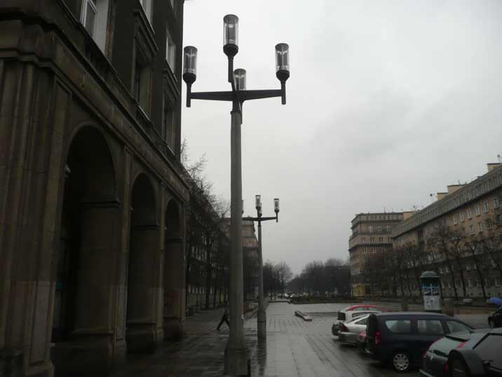 Plac Centralny on a rainy day with a promenade for shops and street light posts that match the design of the Square