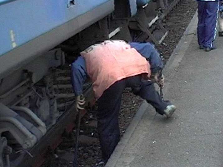 Engineer checking the trains brakes with a sledgehammer