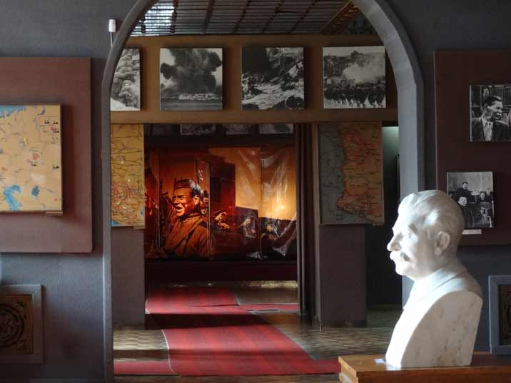 Stalin bust with maps and photos of the second World War in the background