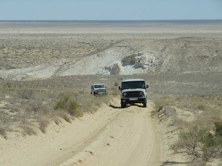 UAZ 469 4x4 cars climbing a hill on the former Aral Sea lakebed