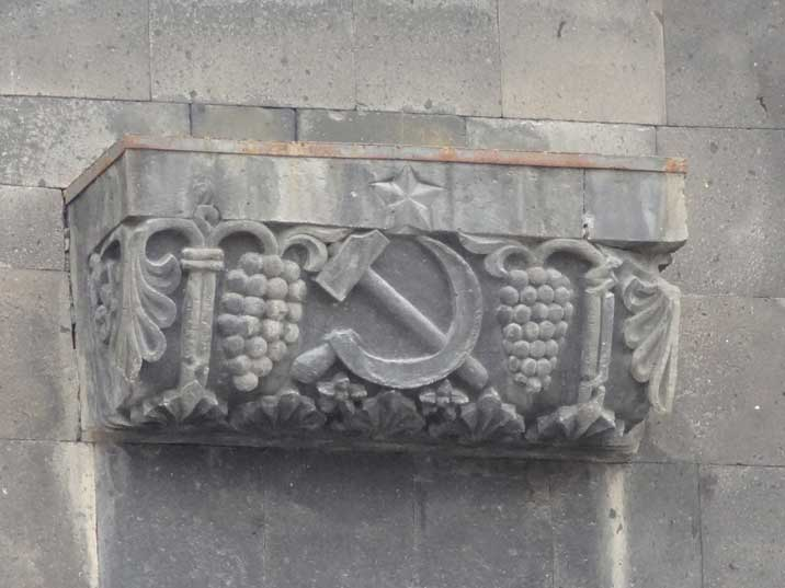 A decoration with the Soviet Hammer and Sickle carved out of stone on the pedestal of the Mother Armenia Statue