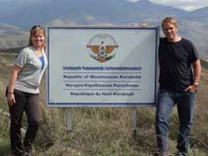 Posing with the border sign on the Nagorno Karabakh - Armenian border with beautiful mountains in the background