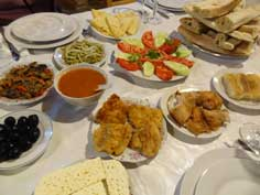A table served with Georgian dishes like Khachapuri, Olives, Badrijan Nigzit, Sulguni cheese and Mchadi corn bread