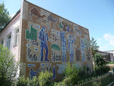 Soviet era fresco's with a cosmonaut on a house in Karkaralinsk