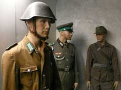 Three East German Border Guards dressed in different uniforms